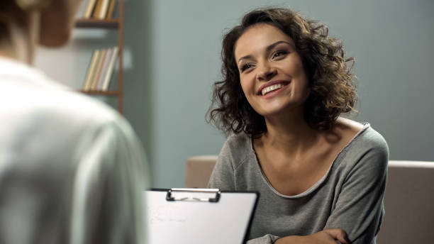 Young happy lady talking with psychologist at clinic, session of rehab therapy Young happy lady talking with psychologist at clinic, session of rehab therapy dependency stock pictures, royalty-free photos & images