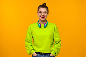 istock Young happy laughing girl in green neon sweatshirt and jeans, wearing blue wireless headphones around neck, keeoing hands in pockets, isolated on yellow background 1247694591