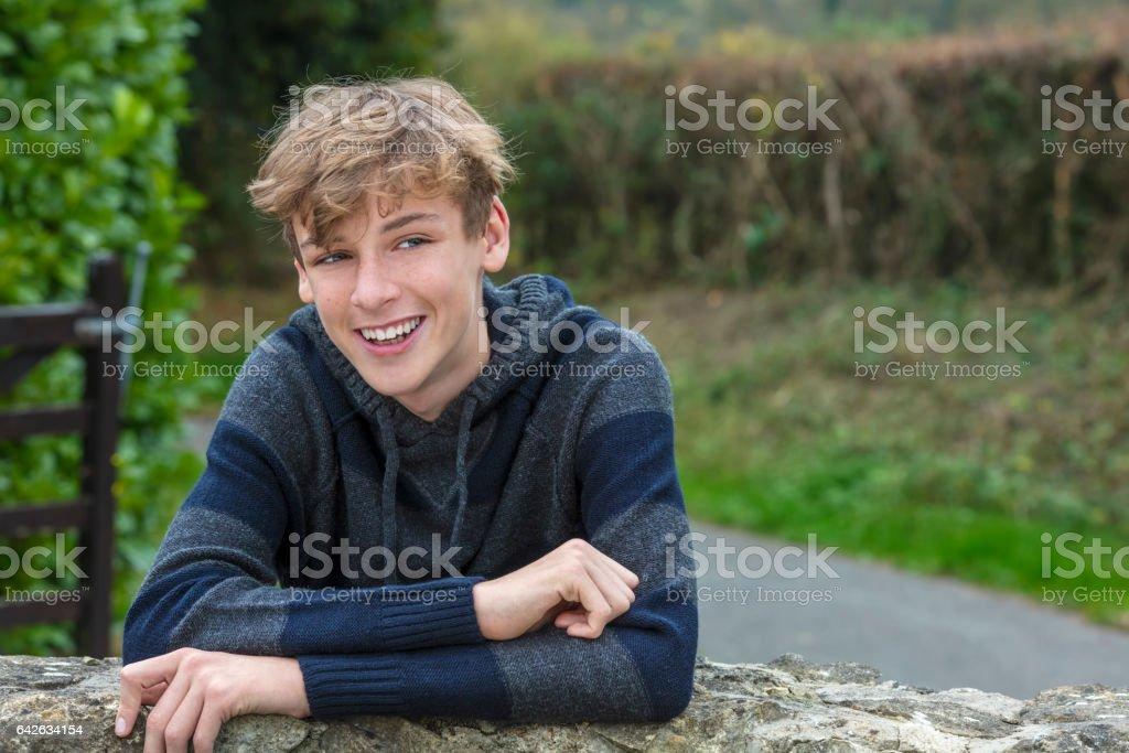 Glücklich lachende lächelnde Teenager männliche junge blonde Kind außerhalb stützte sich auf eine Wand im Herbst Herbst Sonnenschein – Foto