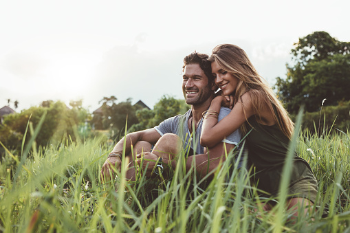 Young happy lovers sitting on meadow