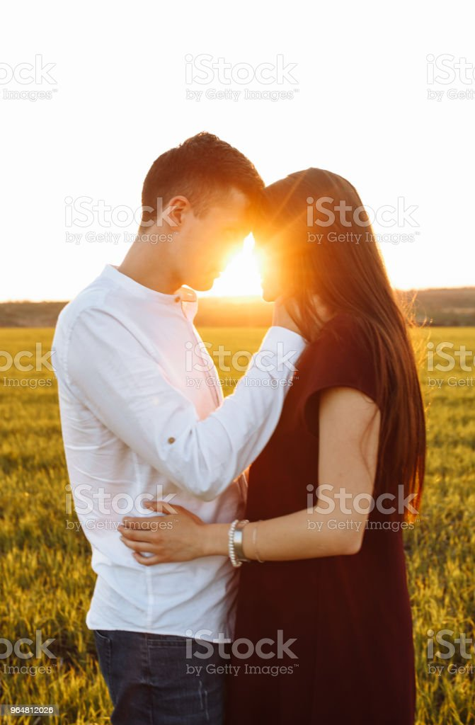 young, happy, loving couple, at sunset, standing in a green field, against the sky, in the arms, and looking at each other, advertising and inserting text royalty-free stock photo