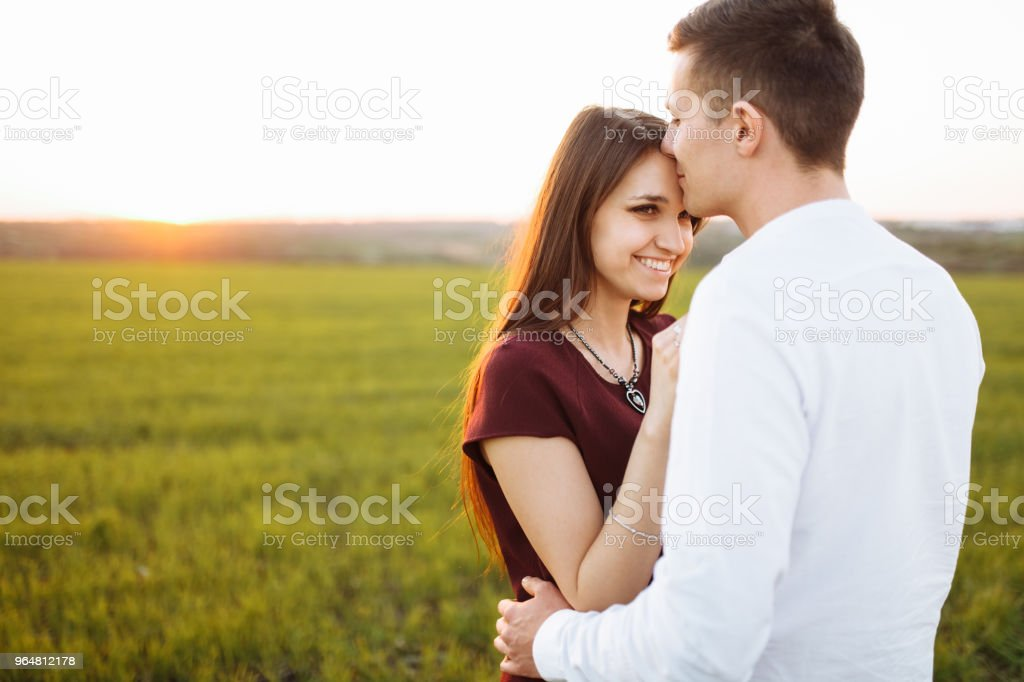 young, happy, loving couple, at sunset, standing in a green field, against the sky, in the arms, and enjoying each other, advertising and inserting text royalty-free stock photo