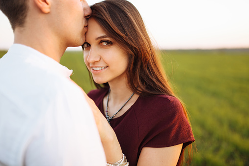 Young Happy Loving Couple At Sunset Standing In A Green Field Against The Sky In The Arms And Enjoying Each Other Advertising And Inserting Text Stock Photo - Download Image Now