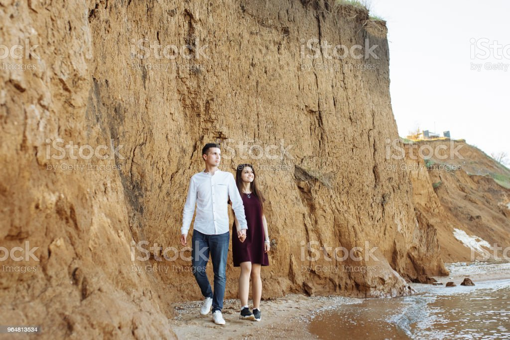young, happy, loving couple, near the sand wall, on the sea, holding hands go and look at each other, advertising and inserting text royalty-free stock photo