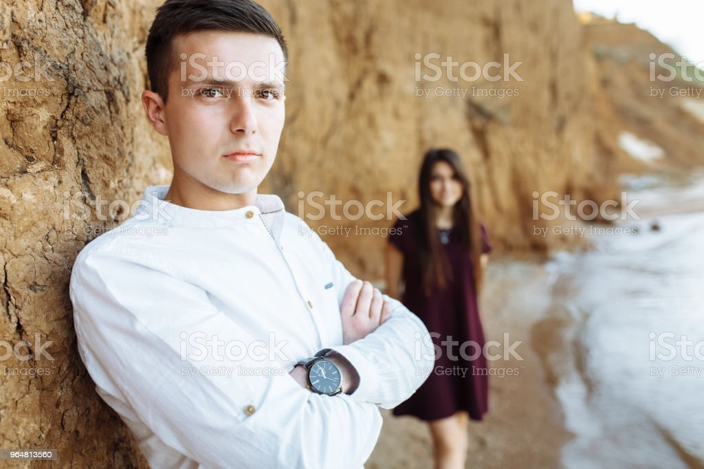 young, happy, loving couple, near the sand wall, on the sea, posing, advertising and inserting text royalty-free stock photo