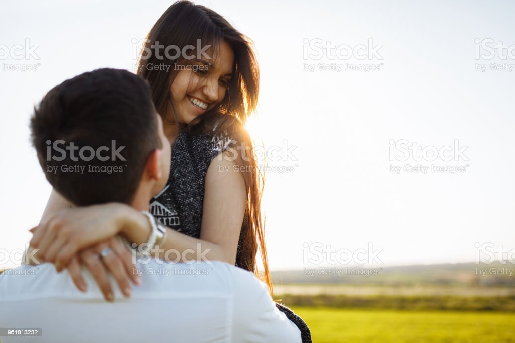 young, happy, loving couple, outdoors, man holding a girl in his arms , and enjoying each other, advertising, and inserting text royalty-free stock photo