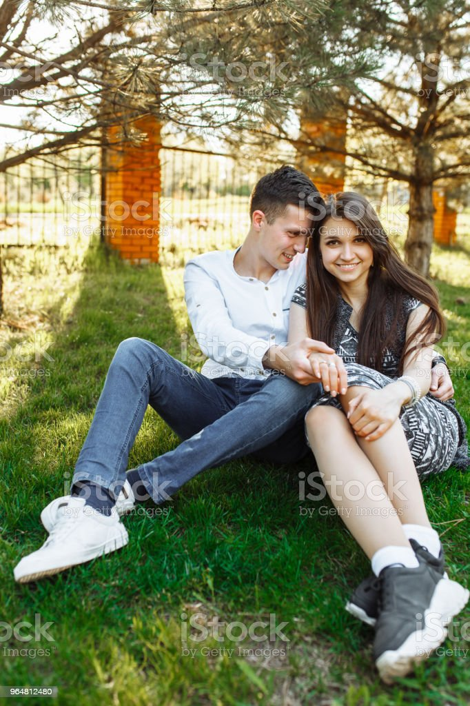 young, happy, loving couple, sitting together on the grass in the Park, and enjoying each other, advertising, and inserting text royalty-free stock photo