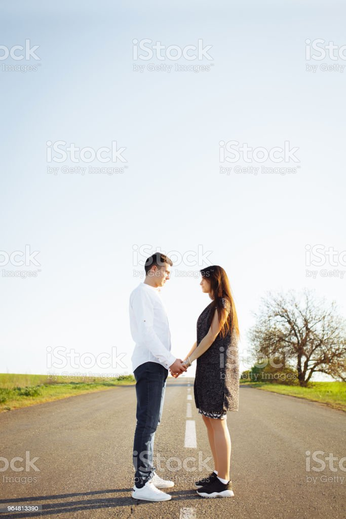 young, happy, loving couple standing on the road holding hands and looking at each other, advertising and inserting text royalty-free stock photo