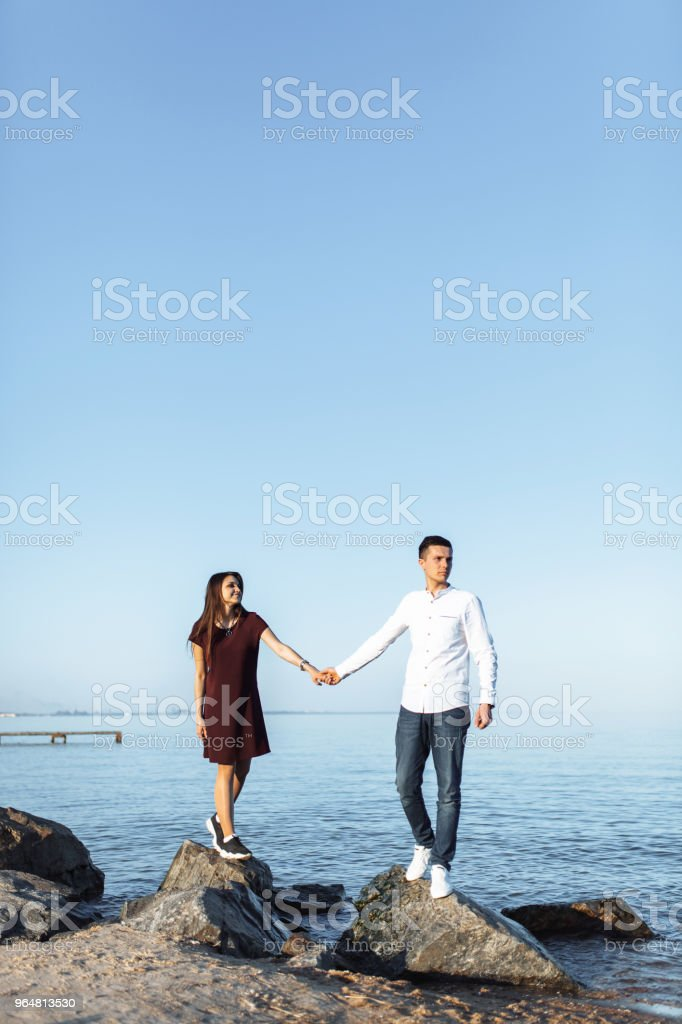 young, happy, loving couple standing on the rocks at sea, in the arms, and looking at each other, advertising and inserting text royalty-free stock photo