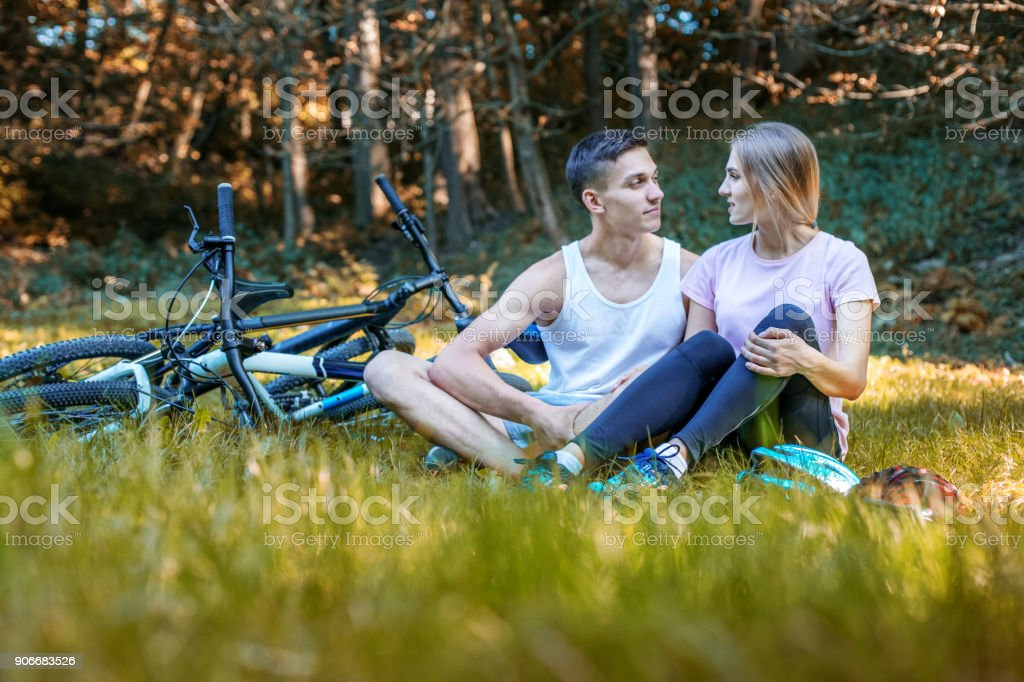 Young Happy Loving Couple. Walking in the park on bicycles. Comm stock photo