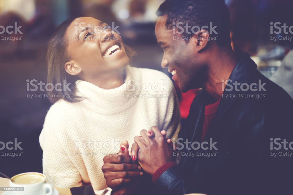 Young happy man and woman laughing together while sitting in modern restaurant during coffee break, cheerful couple in love with smiles on faces enjoying rest and good day while relaxing in bar stock photo
