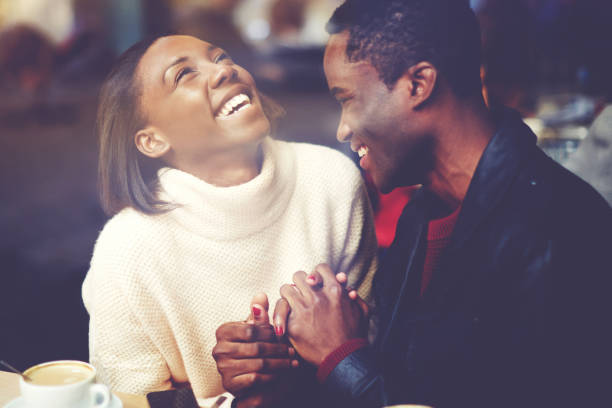 young happy man and woman laughing together while sitting in modern restaurant during coffee break, cheerful couple in love with smiles on faces enjoying rest and good day while relaxing in bar - dating stock photos and pictures