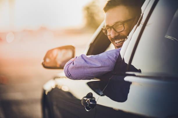 glücklich jüngling autofahren bei sonnenuntergang. - berufsfahrer stock-fotos und bilder