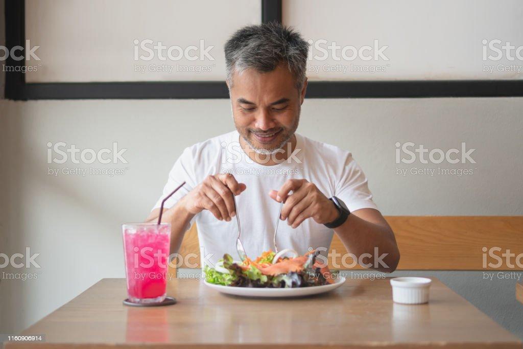Ung lycklig man njuter i en hälsosam måltid - Royaltyfri Asiatiskt och indiskt ursprung Bildbanksbilder