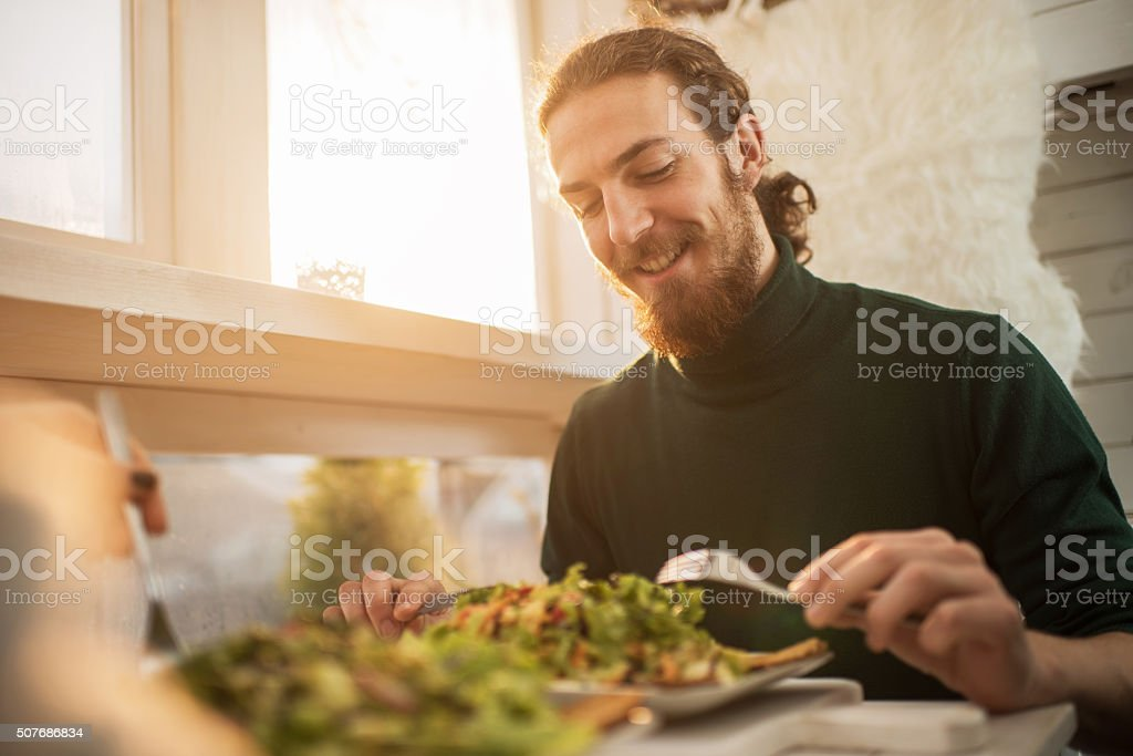 Young happy man enjoying in a healthy meal. stock photo
