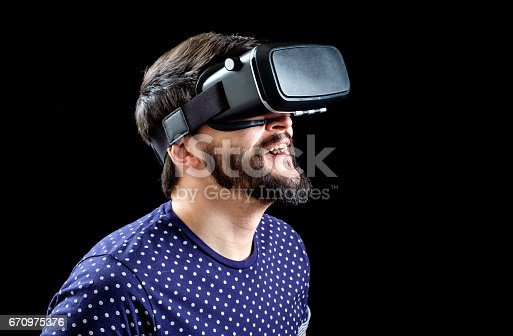 istock Young happy man experiencing virtual reality through a VR headset isolated on black 670975376