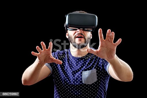 istock Young happy man experiencing virtual reality through a VR headset isolated on black 686259862