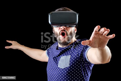 istock Young happy man experiencing virtual reality through a VR headset isolated on black 686259882