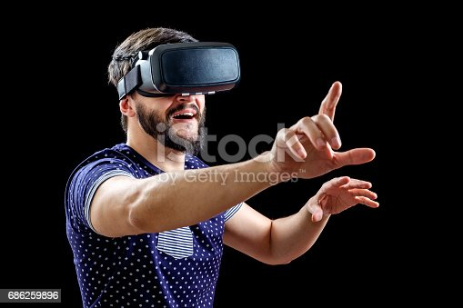 istock Young happy man experiencing virtual reality through a VR headset isolated on black 686259896