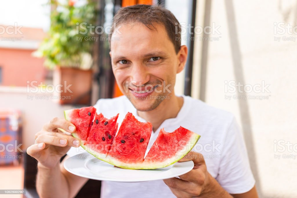 Young happy man in white summer shirt smiling eating vibrant colorful red watermelon slice outside in Italy villa, sunny sunlight stock photo