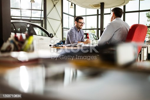 Happy male customer communicating with salesman during a meeting in a car showroom.