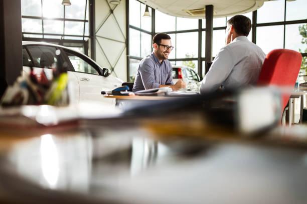 Genç mutlu adam bir showroom araba satıcısı konuşuyor. stok fotoğrafı