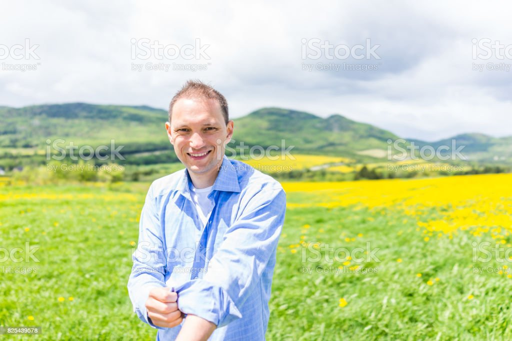 Young happy man tucking sleeves of shirt by field hills of yellow dandelion flowers in summer stock photo