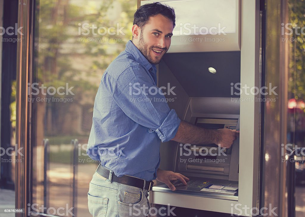 Young happy man using ATM - foto de stock