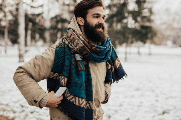 Young, happy man walking in the park during winter stock photo