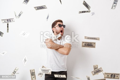 969671638 istock photo young happy man with a beard in white shirt standing under money 643924164