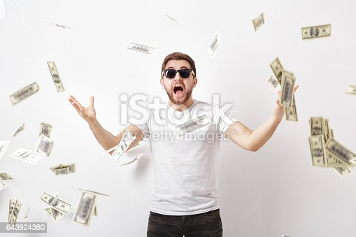 969671638istockphoto young happy man with a beard in white shirt standing under money 643924380