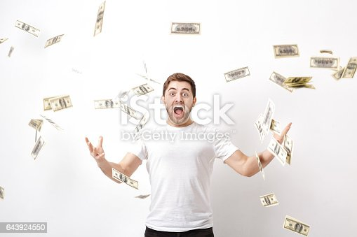 969671638 istock photo young happy man with a beard in white shirt standing under money 643924550