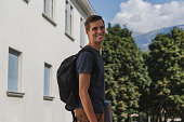 young happy man with backpack walking to school after summer holidays