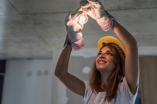 Young happy manual worker repairing light in renovating apartment. Happy female electrician tightening light bulb during home renovation process. power occupation stock pictures, royalty-free photos & images