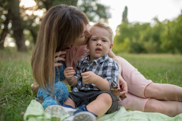 young happy mum and her boy  in the park - dtephoto stock photos and pictures