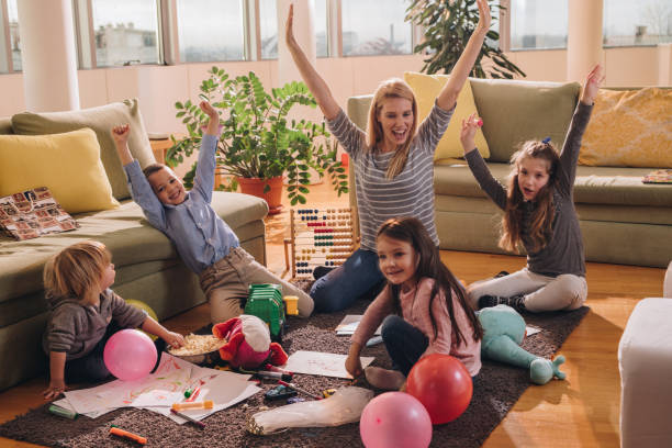 Young happy nanny having fun with small kids in the living room. stock photo