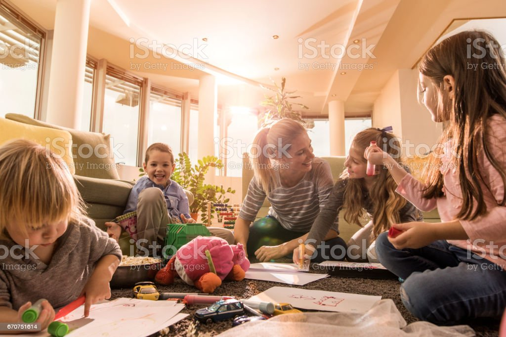 Young happy nanny playing with small kids in the living room. stock photo