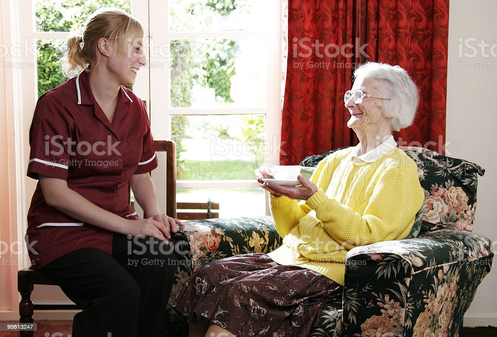 Young happy nurse and senior lady chatting in care home royalty-free stock photo