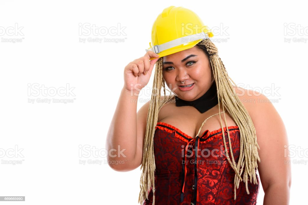Young happy fat Asian construction woman smiling while holding safety helmet and wearing sexy costume stock photo