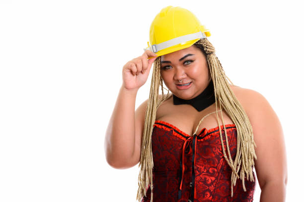 young happy fat asian construction woman smiling while holding safety helmet and wearing sexy costume - builders stock photos and pictures