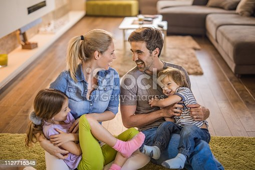 1159543952istockphoto Young happy parents having fun while tickling their kids at home. 1127715348