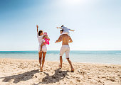 Cheerful parents enjoying at the beach with their little children. Man is carrying little boy on his shoulders. Copy space.