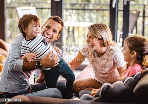 1159543952istockphoto Young happy parents having fun with their small kids in the living room. 1175416514