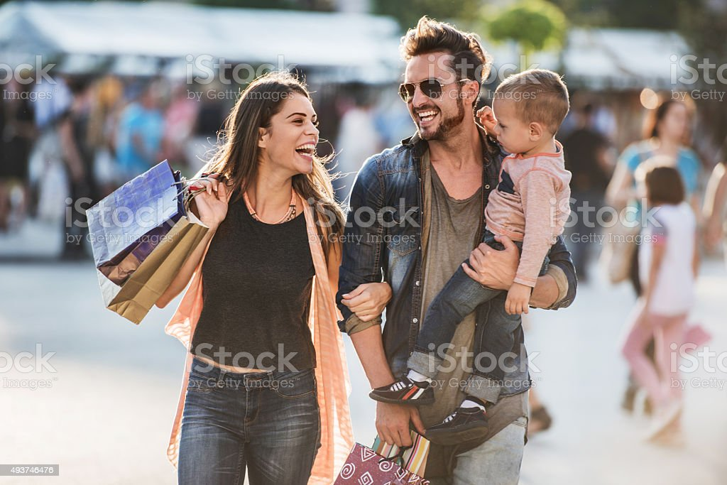 Young happy parents having fun with their son in shopping. stock photo