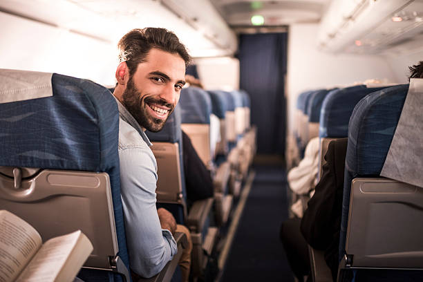 Young happy passenger flying in the airplane. Happy man traveling by plane and turning towards the camera while looking at it. passenger stock pictures, royalty-free photos & images