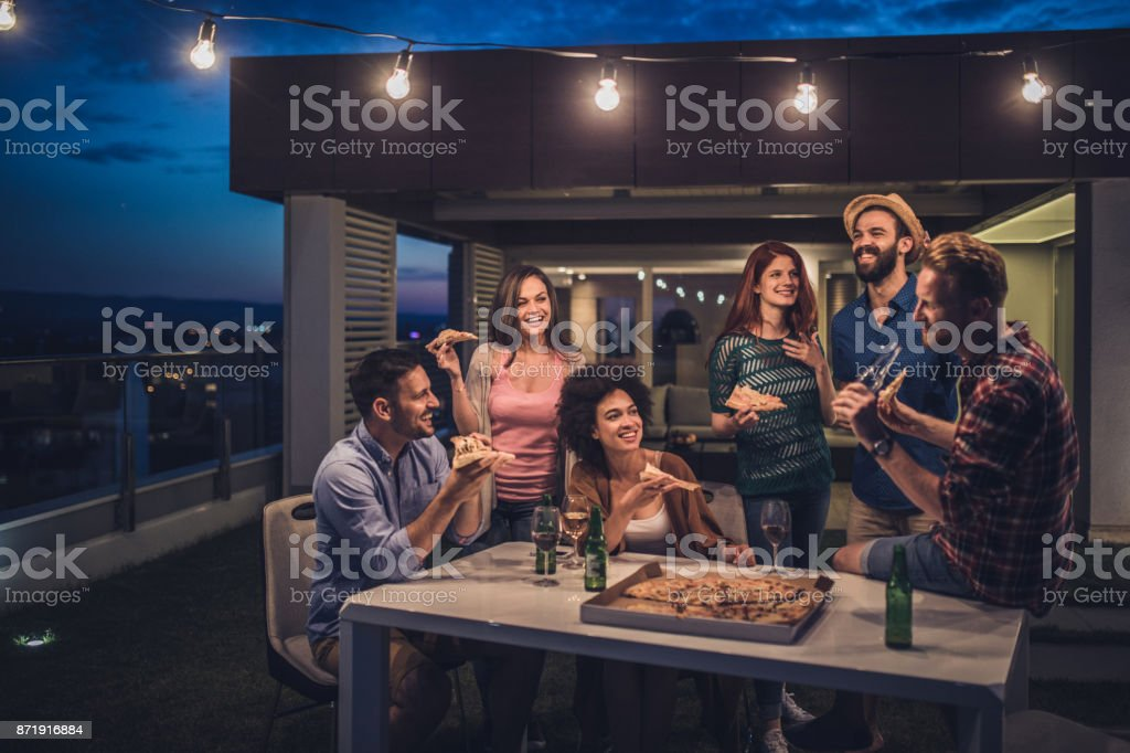 Young happy people having a dinner party during the night on a terrace. stock photo