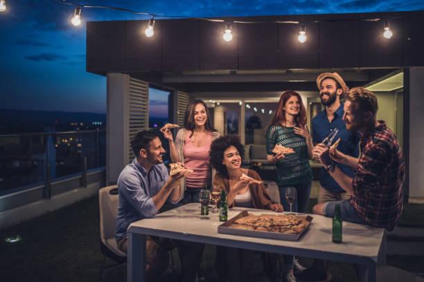 junge glückliche menschen, die mit einem abendessen feiern in der nacht auf der terrasse. - terrassen lichterketten stock-fotos und bilder