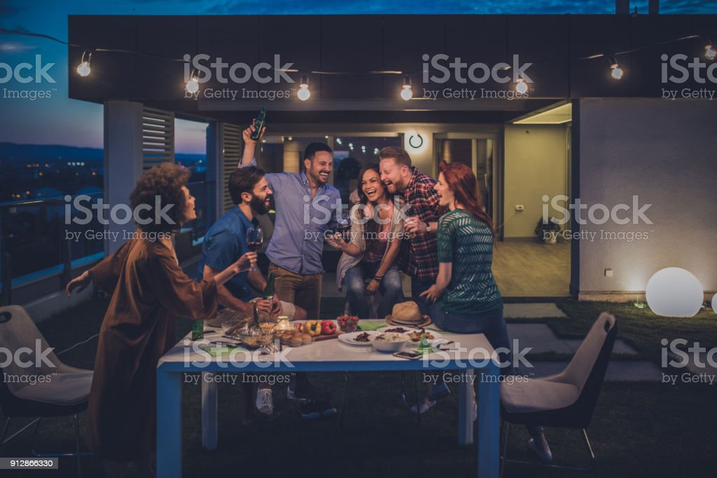 Young happy people having fun while dancing on a night party at penthouse balcony. stock photo