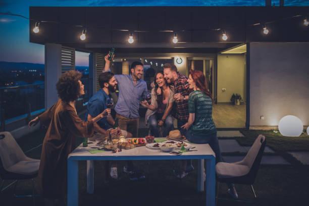 junge glückliche menschen, die spaß beim tanzen in einer nacht party im penthouse balkon. - terrassen lichterketten stock-fotos und bilder