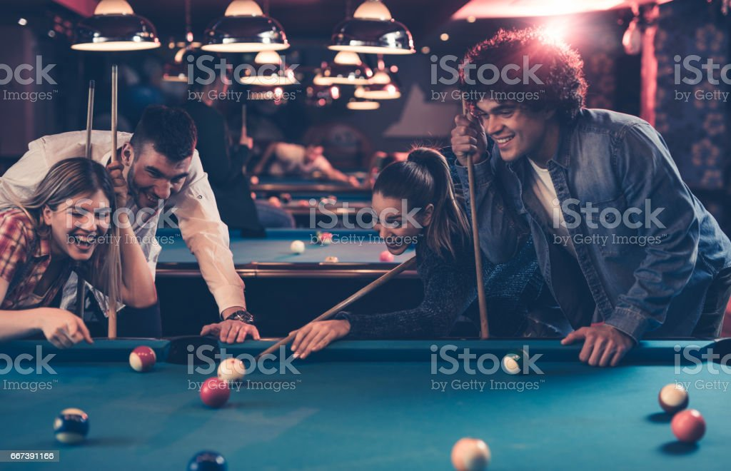 Young happy people having fun while playing billiard in a pub. stock photo